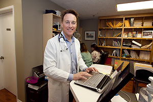 Physician standing with laptop.